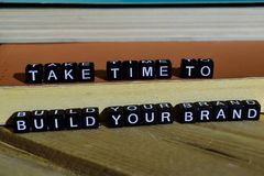 stock image of  take time to build your brand on wooden blocks. motivation and inspiration concept
