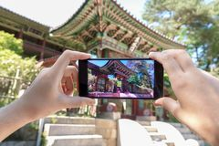 stock image of  taking photo of korean architecture with mobile phone. tourism and digital technologies