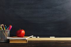 stock image of  teacher`s desk with writing materials, a book and an apple, a blank for text or a background for a school theme. copy space
