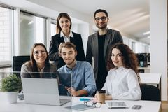 stock image of  teamwork concept.young creative coworkers working with new startup project in modern office and looking at camera