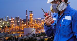 stock image of  technician with gas mask and walkie talkieagainst petrochemical