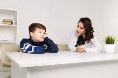 stock image of  teen boy talking to his therapist. social worker and patient.