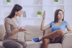 stock image of  teen girl showing stop gesture to angry mother