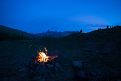stock image of  tent and burning camp fire at dusk on the mountains. summer adventures and exploration in the alps. selective focus on fire, color