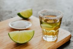 stock image of  tequila shot, mexican alcoholic strong drinks and pieces of lime with salt in mexico