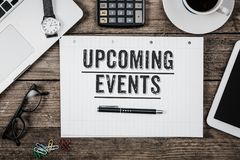 stock image of  text upcoming events written in notepad, office desk with comput