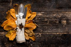 stock image of  thanksgiving meal setting. seasonal table setting. thanksgiving autumn place setting with cutlery and colorful fall fall leaves.