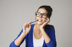 stock image of  thinking business woman looking up, pensive young girl in glasses dream over gray background