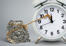 stock image of  time on alarm clock stop by stone, delay concept
