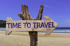 stock image of  time to travel wooden sign with a beach on background