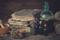stock image of  tincture bottles, assortment of dried healthy herbs, old books, wooden mortar, sack of medicinal herbs. herbal medicine.