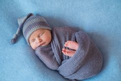 stock image of  tiny sleeping newborn baby covered with rich purple coloured wrap