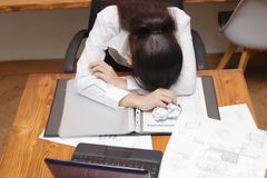 stock image of  tired overworked young asian business woman bend down head on workplace in office.