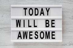 stock image of  `today will be awesome` words on lightbox over white wooden surface, top view.