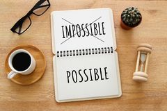 stock image of  top view image of open notebook with the text impossible, cutting the word im so it written possible. success and challenge concep
