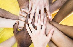 stock image of  top view of multiracial stacking hands - international friendship