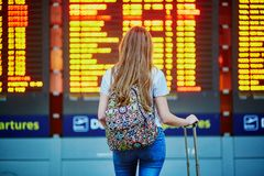 stock image of  tourist girl with backpack and carry on luggage in international airport, near flight information board