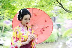 stock image of  traditional asian japanese beautiful geisha woman bride wears kimono hold a red umbrella in a summer nature