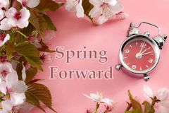 stock image of  turn clocks on hour ahead, star of daylight savings time change and reminder to spring forward concept with alarm clock on pink