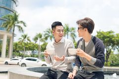 stock image of  two adult male friends sit talking over coffee outside cafe