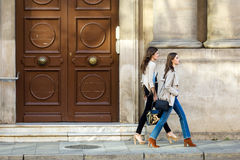 stock image of  two beautiful young women walking and talking in the street.