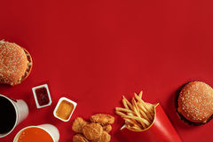 stock image of  two hamburgers and french fries, sauces and drinks on red background. fast food. top view, flat lay with copyspace