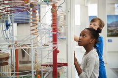 stock image of  two kids looking at a science exhibit, waist up