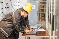 stock image of  two maintenance engineers inspect relay protection system with l