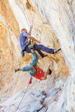 stock image of  two male climbers hanging on a rope.