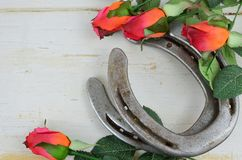 stock image of  two old horse shoes paired with silk red roses on a white-washed rustic wooden background