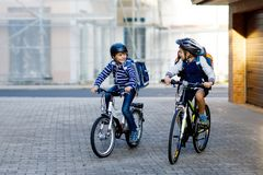 stock image of  two school kid boys in safety helmet riding with bike in the city with backpacks. happy children in colorful clothes