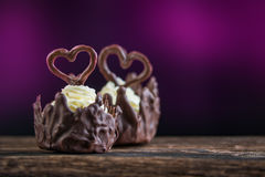 stock image of  two sweet chocolate desserts filled with white cream and with hearts on purple background, valentines or wedding cake