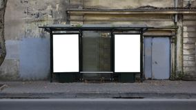 stock image of  two vertical blank white billboards at bus stop on old city street