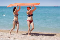 stock image of  two women in swimsuits carrying inflatable raft over their heads