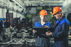 stock image of  two workers at an industrial plant with a tablet in hand, working together manufacturing activities