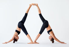 stock image of  two young women doing partner yoga asana downward facing dog