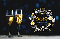 stock image of  2019 typography art. two glasses of champagne dark glow lights b