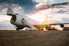 stock image of  unloading wide body transport cargo plane in the morning sun