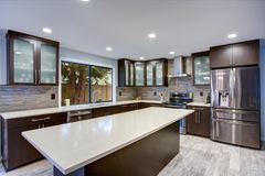 stock image of  updated contemporary kitchen room interior in white and dark tones.
