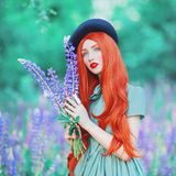 stock image of  valentines day background. young fairy redhead girl with very long hair on lupine background. valentines day beauty woman in mint