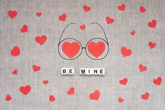 stock image of  valentines day mockup, greeting card with many red hearts, two big heart in doodle eyeglasses and text be mine on linen fabric
