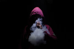 stock image of  vaping man holding a mod. a cloud of vapor. black background. vaping an electronic cigarette with a lot of smoke