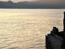 stock image of  varenna, italy  march 30 2019 romantic couple sits to contemplate the sunset at lake como