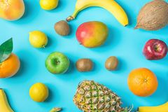 stock image of  variety of different tropical and seasonal summer fruits. pineapple mango coconut oranges lemons apples kiwi bananas scattered