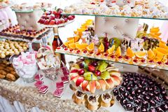 stock image of  variety of sweet desserts with fruits and alcohol drinks on the