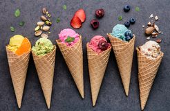 stock image of  various of ice cream flavor in cones blueberry ,strawberry ,pistachio ,almond ,orange and cherry setup on dark stone background .