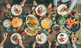 stock image of  friends eating at thanksgiving day table with vegetarian snacks