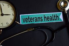 stock image of  veterans health on the print paper with healthcare concept inspiration. alarm clock, black stethoscope.