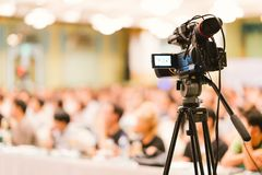 stock image of  video camera set record audience in conference hall seminar event. company meeting, exhibition convention center concept