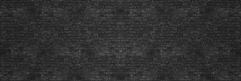 stock image of  vintage black wash brick wall texture for design. panoramic background for your text or image.